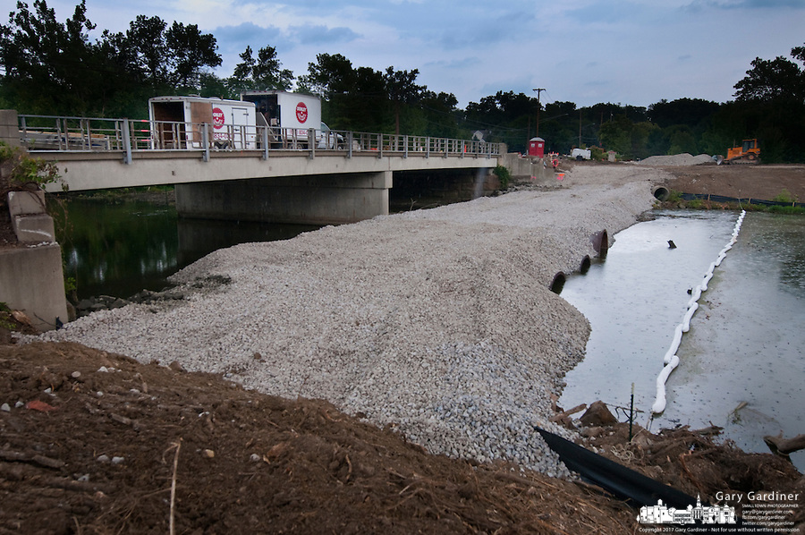 A temporary gravel bridge spans Alum Creek for trucks and demolition equipment.