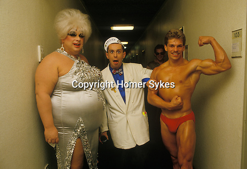 """Holly Johnson, lead singer in the pop band Frankie Goes to Hollywood, during a break in recording a TV special in Hamburg Germany. Seen here with Divine who performer the song """" You Think Your A Man"""" and a local well built young male. 1980s"""