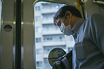 A commuter wearing a mask sleeps inside a suburb train on May 26, 2020 in Tokyo Japan. It's the first day after the Japanese government lifted the state of emergency during the coronavirus (also knows as Covid-19) pandemic. Tokyo, JAPAN 26 May 2020. (Photo by Nicolas Datiche/AFLO) (JAPAN) FRANCE OUT