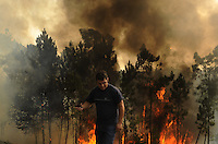 A man is seen around the area where a fire burns, in Salvador nord of Portugal, on august 09, 2010. (c) Pedro ARMESTRE