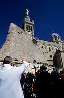 Priest leading prayer outside the Notre-dame de la Garde basilica, Marseille, France.