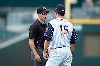 Umpire Brennan Miller explains a call to Charlotte Knights manager Mark Grudzielanek (15) during the game against the Durham Bulls at BB&T BallPark on May 27, 2019 in Charlotte, North Carolina. The Bulls defeated the Knights 10-0. (Brian Westerholt/Four Seam Images)