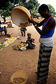 The Gambia. Rural market; woman pouring peanuts (groundnuts) from a half gourd.