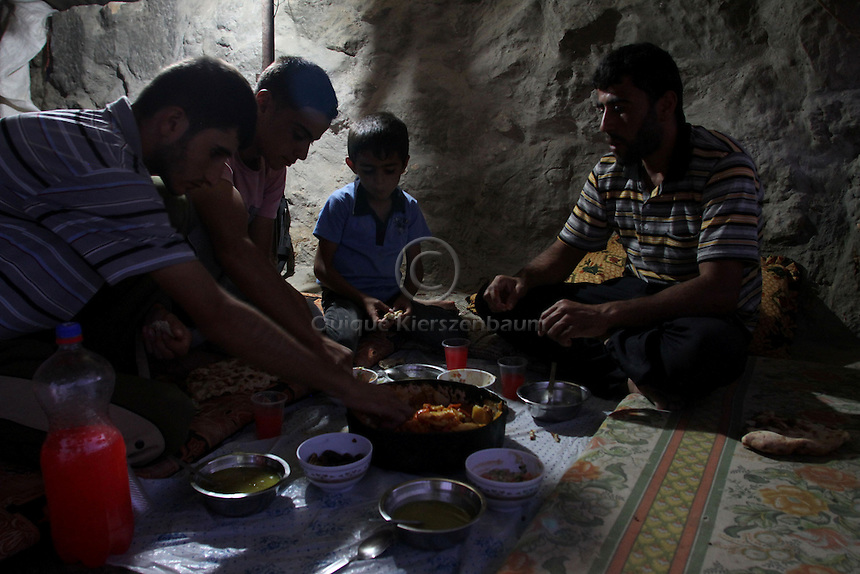 """Mahmod Ahmad Issa and his male family members eat Iftar meal during Ramadan in his cave in Jenba a Palestinian town of 50 families seats in an area called by the IDF as """"Firing Zone 918"""" and is located in the southern Hebron hills near the town of Yatta.  Spread over 30,000 dunams, it includes twelve Palestinian villages.  According to OCHA figures, 1,622 people lived in the area in 2010, and according to local residents the number of inhabitants currently stands at about 1,800. For over a decade, the residents of twelve uniquely traditional Palestinian villages in the area of Masafer-Yatta in the south Hebron hills have lived under the constant threat of demolition, evacuation, and dispossession.<br /> <br /> The State's insistence on evacuation of Firing Zone 918 in part or in whole, if acceptance by the HCJ, might result in an immediate humanitarian disaster for almost two thousand souls, the destruction of villages, and the eradication of a remarkable way of life that has endured for centuries."""