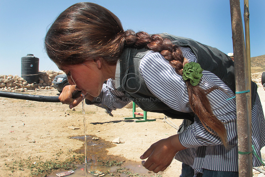 """A Palestinian girl drinks water from a pipe at Jenba's school in the South Hebron Hills, Jenba a Palestinian town of 50 families seats in an area called by the IDF as """"Firing Zone 918"""" and is located in the southern Hebron hills near the town of Yatta.  Spread over 30,000 dunams, it includes twelve Palestinian villages.  According to OCHA figures, 1,622 people lived in the area in 2010, and according to local residents the number of inhabitants currently stands at about 1,800. For over a decade, the residents of twelve uniquely traditional Palestinian villages in the area of Masafer-Yatta in the south Hebron hills have lived under the constant threat of demolition, evacuation, and dispossession.<br /> The State's insistence on evacuation of Firing Zone 918 in part or in whole, if acceptance by the HCJ, might result in an immediate humanitarian disaster for almost two thousand souls, the destruction of villages, and the eradication of a remarkable way of life that has endured for centuries. Photo by Quique Kierszenbaum."""