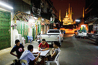 Thailand. Bangkok. A group of young teenagers (boys and girl), all of chinese origin, sit on plastic chairs at night and play with their mobiles phones. In the back, illuminated with electric lights stands Wat Pho, also known as Wat Phra Chetuphon, or The Temple of the Reclining Buddha, which is a Buddhist temple. An alley with shophouse units for business in wholesale, retail and service sectors. Cars and pick-up vans parked. Tha Tian's community is located in the downtown area and in the center of the urban historic district, called Koh Rattanakosin. The Tha Thian is surrounded by a major heritage and tourist site, Wat Pho. 30.03.09  © 2009 Didier Ruef