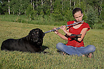 Black Labrador retriever (AKC) sitting next to a 13 year old girl playing the flute.  Summer.  Winter, WI.