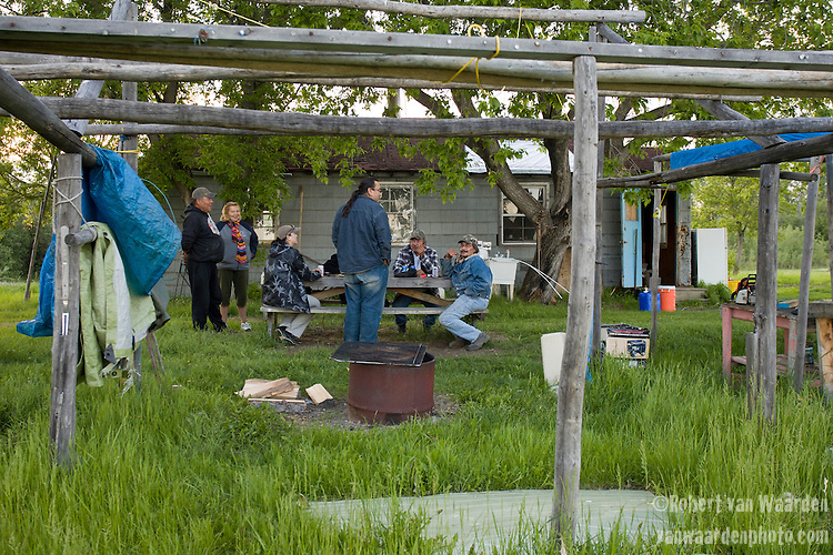Residents of Jackfish enjoy an evening beer. Jackfish is part of the reserve for the Dineh (Chipewyan) peoples of Northen Alberta. In the foreground is a drying rack for fish.