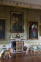 Detail of some of the 18th century portraits that hang from the damask clad walls of the Great Drawing room at Badminton House. The Italian chimney piece was designed by James Byres in 1773