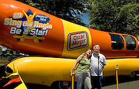 Two fans (no model releases) sing the Oscar Mayer song at Speed Street 2007. For several days leading up to the May races at the Lowe's Motor Speedway, uptown Charlotte streets are transformed into a showcase of motor sports and non-stop entertainment. ..Photo taken in 2007. Photographer also has images from 2008.
