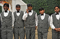 Uniformed waiting staff including one talking on a mobile phone at a reception after the wedding ceremony of British/Punjabi couple Lindsay and Navneet Singh at Grewal Farms in Amritsar.