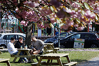 Pictured: People enjoy the sunny weather having a drink in Mumbles near Swansea, Wales, UK. Monday 26 April 2021<br /> Re: Lockdown rules caused by the Covid-19 Coronavirus pandemic have been relaxed, with outdoors pubs, restaurants and cafes now open in Wales, UK.
