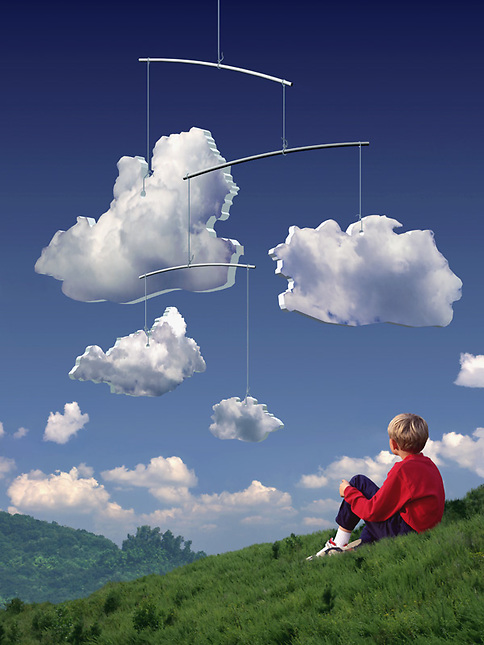 Boy on hill watching mobile made of clouds