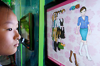 China. Shanghai. World Expo. Expo 2010 Shanghai China.  China Pavilion. Inside the Fujian pavilion, a young chinese girl looks on the computer screen and chooses the various dress and clothes for her model. 25.06.10 © 2010 Didier Ruef