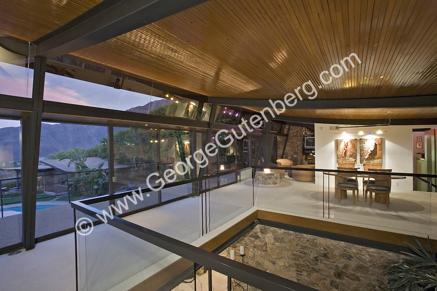 Contemporary living room with walls of glass and steel beam ceiling