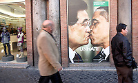 Un fotomontaggio raffigurante il presidente cinese Hu Jintao, a sinistra, che bacia sulla bocca il presidente degli Stati Uniti Barack Obama, parte di una campagna pubblicitaria della Benetton, in uno dei suoi negozi a Roma, 17 novembre 2011..People pass past a photo montage of a new ad campaign of Italian clothing company Benetton, showing US president Barack Obama, right, and Chinese president Hu Jintao kissing each other on the lips, in a Benetton shop in Rome, 17 November 2011..UPDATE IMAGES PRESS/Riccardo De Luca