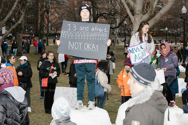 """People gather during the March For Our Lives protest and demonstration in Boston Common in Boston, Massachusetts, USA, on Sat., March 24, 2018. The march was held in response to recent school gun violence. Here, children hold signs reading, """"13 and afraid... not okay."""" and """"Never again."""""""