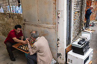 Albania. Tirana. Town center. Two men play chess on board in a small alley. Chess is a two-player strategy board game played on a chessboard, a checkered gameboard with 64 squares arranged in an 8×8 grid. An elderly man smokes a cigarette on the sidewalk. Electronics equipments and tools for sale at street market. Tirana is the capital and most populous city of the Republic of Albania. The city is also the capital of the surrounding county of Tirana, one of 12 constituent counties of the country. 20.5.2018 © 2018 Didier Ruef