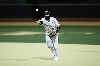 Bobby Seymour (3) of the Wake Forest Demon Deacons tosses the ball towards first base during the game against the Louisville Cardinals at David F. Couch Ballpark on March 6, 2020 in  Winston-Salem, North Carolina. The Cardinals defeated the Demon Deacons 4-1. (Brian Westerholt/Four Seam Images)
