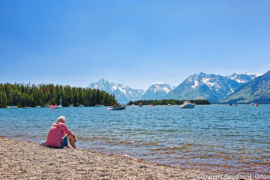 Woman sitting on shoreline of Jackson Lake at Leeks Marina.  Best pizza in a remote location.  Grand Teton National Park, United States, Wyoming.