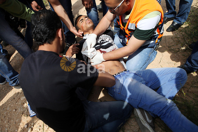 Palestinian medics treat a wounded protester during clashes with Israeli security forces following a demonstration marking Palestinian Prisoners' Day, in the West Bank village of Bilin, near Ramallah on April 17, 2015. Palestinian human rights groups say 6,000 Palestinian prisoners remain in Israeli prisons and detention camps. Photo by Shadi Hatem