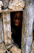 Bacaja village, Amazon, Brazil. A child looks through the hole in the wall of a house; Xicrin tribe.