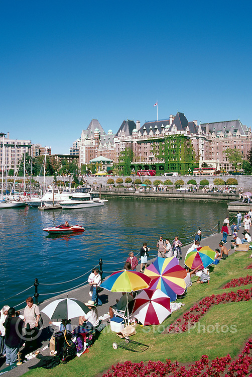 Victoria, BC, Vancouver Island, British Columbia, Canada - Tourists walking along The Lower Causeway and Inner Harbour, past Artisan Vendors and Fairmont Empress Hotel