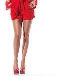 Closeup of long legs of a young woman wearing sexy red clothes and red high heel shoes isolated on white background Image © MaximImages, License at https://www.maximimages.com