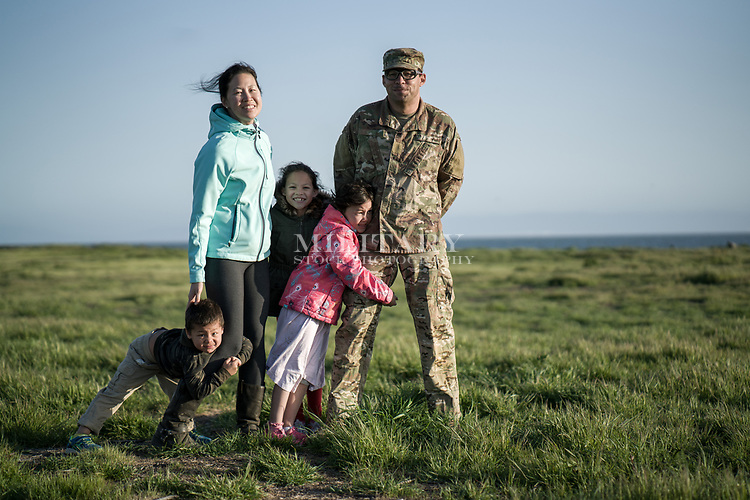 Loving husband in uniform at the beach with his wife and children