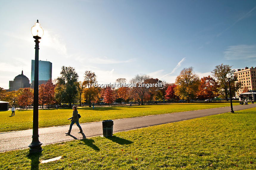 Woman walking at a good pace along the Commons Park in Boston, is a suny autumn day with perfect blue sky