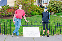 """People stand near a sign reading """"We support Governor Baker's Orders"""" while looking on as people gather for an anti-lockdown protest organized by the alt-right group Super Happy Fun America near the home of Massachusetts governor Charlie Baker in Swampscott, Massachusetts, on Sat., May 16, 2020. The protest was in defiance of Massachusetts orders mandating face coverings and social distancing and prohibiting gatherings larger than 10 people during the ongoing Coronavirus (COVID-19) global pandemic. The state's stay-at-home order is expected to be updated on May 18, 2020, with a phased reopening plan issued by the governor as COVID-19 cases continue to decrease. Anti-lockdown protests such as this have become a conservative cause and have been celebrated by US president Donald Trump. Many of the protestors displayed pro-Trump messages or wore Trump campaign hats and shirts with phrases including """"Trump 2020"""" and """"Keep America Great."""" Super Happy Fun America, organizers of the protest, are an alt-right organization best known for creating the 2019 Boston Straight Pride Parade."""