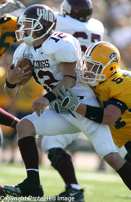 University of Minnesota Duluth's Ted Schlafke (12) is brought down by Augustana's Chris Janish in the second quarter of their NCC game Saturday afternoon at Howard Wood Field in Sioux Falls. (photo by Dave Eggen/Inertia)