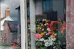 Plastic Flowers never wilt. Domestic window display. Chagford, Devon. UK. Nov 2012