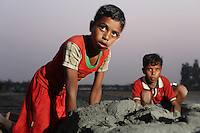 Children work in a brick factory, in the Malancha district of eastern Kolkata. As their parents work nearby, children often play in the area, exposing them to harmful materials and waste produced in the industrial process. India. November, 2013