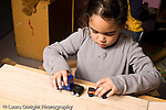 Education Preschool 4-5 year olds girl playing with small toy vehicles horizontal