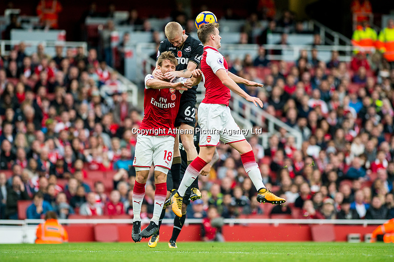 Oliver McBurnie ( centre )  jumps for the ball during the Premier League match between Arsenal and Swansea City at Emirates stadium, London, England, UK. Saturday 28 October 2017