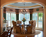 Elegant Breakfast room in traditional home featuring upholstered dining chairs, round table, circular rug, bay window, trey ceiling with recessed lighting