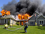 Video at You Tube of these photos http://www.youtube.com/watch?v=QRtfDhBJuuk&feature=youtube_gdata<br /> <br /> <br /> Fire engulfs this large contemporary style home at 27 Abbott Rd in Ellington, CT., Sunday, April 29, 2012. The fire was blowing out of the rear enclosed porch (on my arrival) before a large flash over consumed the house. The house is new construction but the fire had already consumed much of the house before Ellington Fire Department. was on scene. Two occupants and the family dog escaped the house prior to the fire Department arrival, so this was an exterior operation all the way, Strong winds caused a fairly large brush fire behind house into the wood line. Vernon, Crystal Lake, Tolland and South Windsor fire departments were on scene assisting the Ellington Fir Department..Check out pictures of the EFD trying to save the house. (Jim Michaud/@CTNewsAlert)