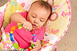 5 month old baby girl closeup in infant seat holding circular colorful teething ring toy in both hands looking at it