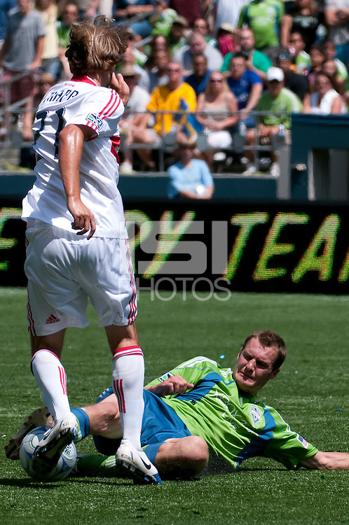 Nate Jaqua (R) of the Seattle Sounders goes for a sweep against Justin Mapp (L) of the Chicago Fire defend in the match at the XBox Pitch at Quest Field on July 25, 2009. The Sounders and Fire played to a 0-0 draw.