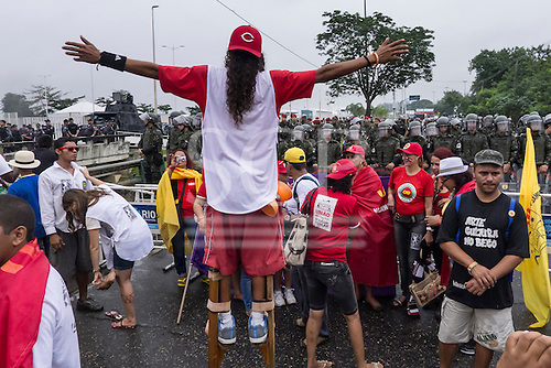 A demonstrator on stilts faces shock troops across a barrier at a demonstration by indigenous people, the Landless People's Movement (MST) and other civil society groups in front of the Riocentro United Nations conference. The demonstrators are kept out of earshot and invisible to the UN conference. United Nations Conference on Sustainable Development (Rio+20), Rio de Janeiro, Brazil, 20th June 2012. Photo © Patrick Cunningham.