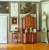 A polished bureau and a pale green grandfather clock stand beneath a wall panel depicting a landscape in this elegant drawing room