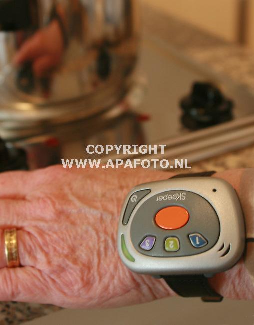 Tolkamer 181006 Een bejaarde bewoonster van verzorgingstehuis Lobede in Tolkamer gebruikt een Diafoon om haar pols. Dit apparaat schakelt bv de electrische kookplaat automatisch uit, waneer de bewonster dat vergeten zou.<br /> Foto frans Ypma APA-foto