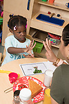 Education Childcare toddler 2s girl working with teacher vocabulary and counting