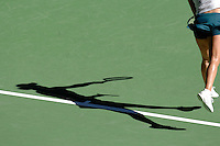 The shadow of a woman serving in tennis on a court.