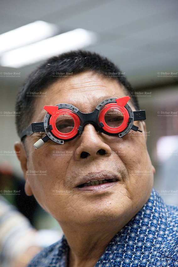 Thailand. Bangkok. Tha Tian Community Center.  Mr. Chul Darunvitit, 69 years old, with chinese origin wears a pair of glasses in order to check his field of vision. Eyes examination during an Ophthalmology sight checkup. Once a month, a Health care program financed by the Bangkok Metropolitan Administration (BMA) offers a free medical checkup by a group of trained doctors and nurses. Tha Tian is a community located in the downtown area and in the center of the urban historic district, called Koh Rattanakosin. 01.04.09 © 2009 Didier Ruef