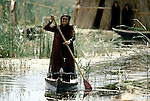 Marsh Arabs. Southern Iraq. Marsh Arab woman standing in boat rowing between traditional reed island homes. Haur al Mamar or Haur al-Hamar marsh collectively known now as Hammar marshes Irag 1984