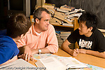 Education High School public male math teacher working with two male students explaining concept horizontal
