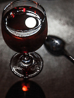 The September full moon, the Harvest Moon, floats as a reflection in a wine glass.
