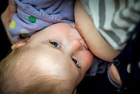 """A close-up of a baby breastfeeding.<br /> <br /> Image from the """"We Do It In Public"""" documentary photography project collection: <br />  www.breastfeedinginpublic.co.uk<br /> <br /> Dorset, England, UK<br /> 17/04/2013"""
